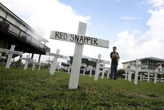 """River Shay, stands in the front yard of his camp with his dog """"Smash"""", while his father Patrick Shay, a seafood business owner from River Ridge"""