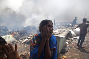 A local resident reacts at the site after a fire broke out in a slum area in New Delhi