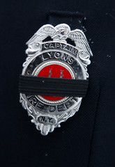 Mourning band is placed over fire department badge during calling hours for Chiapperini and Kaczowka in West Webster