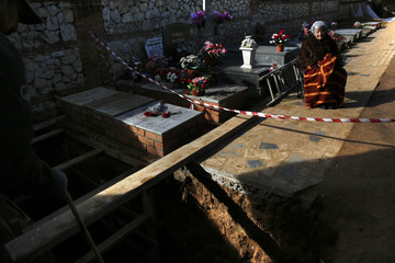 Ascension Mendieta, daughter of Timoteo Mendieta, who was shot in 1939, sits next a grave during the exhumation of her father's remains at Guadalajara's cemetery