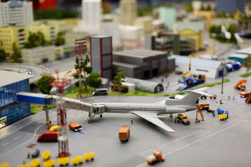 City in miniature. Model of Push back airplane in the airport apron. Tlit shift effect.