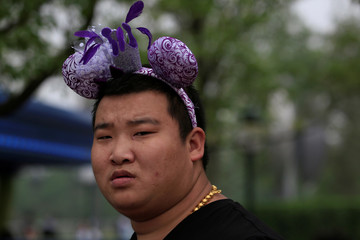 A man wears Mickey Mouse ears after the opening ceremony at Shanghai Disney Resort in Shanghai,