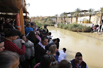 Pilgrims wait for their turns to fill plastic bottles with baptism water after Mass at a baptism site on the Jordan River