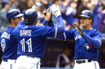 Blue Jays' Johnson gets high fives at home plate by teammates Davis and Arencibia after hitting a two run home run against the Rangers in their American League MLB baseball game in Toronto