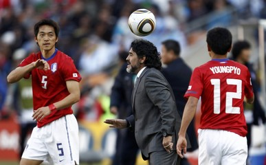 Argentina's coach Maradona shouts instructions to his players between South Korea's Kim and Lee during World Cup match in Johannesburg