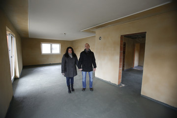 Manuela and Herbert Schmid pose for a picture in their flood-affected living room in Fischerdorf, a suburb of the eastern Bavarian city of Deggendorf