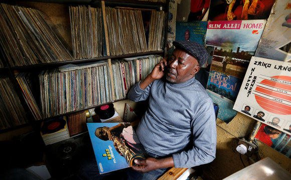 Vendor Rugami talks on his cellphone inside his second-hand vinyl record stall at the Kenyatta Market in Nairobi