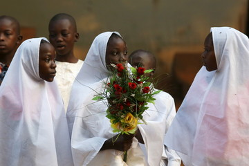 A girl holds a bouquet of flowers as a gift for Pope Francis, prior to his visit at the central mosque in the mostly Muslim PK 5 neighbourhood of the capital Bangui