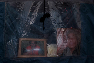 Pictures of Mario Gomez, one of the 33 miners trapped underground in a copper and gold mine, are seen inside a tent at Copiapo