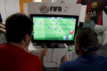 """People play Electronic Arts' """"FIFA"""" video game at the Microsoft Xbox booth at the Electronic Entertainment Expo, or E3, in Los Angeles"""