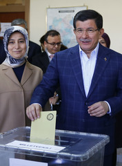 Turkish Prime Minister Ahmet Davutoglu casts his ballot with his wife Sare at a polling station during the parliamentary election in Konya