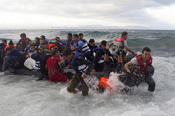 Refugees and migrants struggle to jump off an overcrowded dinghy on the Greek island of Lesbos, after crossing in rough seas from the Turkish coast