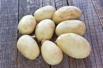 Young potatoes on wooden background