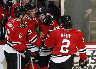 Blackhawks' Kane is hugged by his teammates Toews, Keith and O'Donnell after his goal against the Florida Panthers in the second period of their NHL hockey game in Chicago