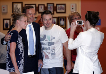 Abbott, who leads the conservative opposition, poses for a photograph with voters before casting his vote on election day at the Freshwater Beach Surf Lifesaving Club in Sydney