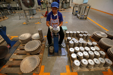 An employee arranges blades for construction at an assembly line at Gang Yan Diamond Tools, a Chinese manufacturing plant, located in the Thai-Chinese Rayong Industrial Zone
