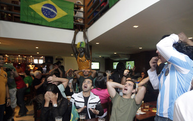 Soccer fans react while watching Argentina and Nigeria play in their World Cup soccer match, in Rio de Janeiro