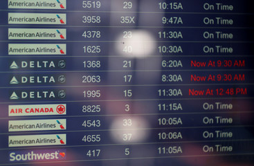 A flight information board shows delays for Delta Airlines flights after the airlines computer systems crashed leaving passengers stranded as flights were grounded globally at Ronald Reagan Washington National Airport in Washington.