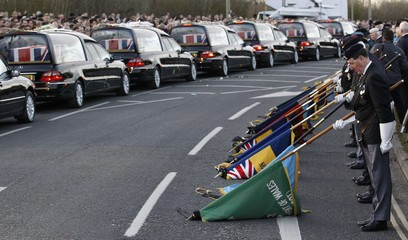 The repatriation cortege carrying the bodies of six British Army soldiers killed in Afghanistan stops at The Memorial Garden in Carterton, near Brize Norton