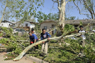 Alan Phillips, Nsilo Hunter Jr., and their father Nsilo Hunter Sr. work to clean up fallen tree limbs from their home that was hit by a tornado in Oklahoma City