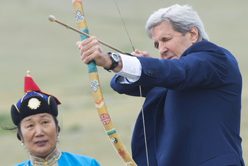 U.S. Secretary of State John Kerry shoots a bow and arrow as he participates in a Naadam ceremony in Ulan Bator