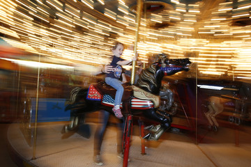A fairgoer rides the merry-go-round during the 100th anniversary of The Eastern States Exposition in West Springfield