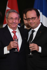 French President Francois Hollande and Cuba's President Raul Castro raise a glass to make a toast during a State dinner at the Elysee Palace in Paris