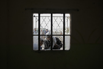 A Palestinian man and boy look through a window frame at the scene where Israeli security officials killed a Palestinian militant last night near Hebron
