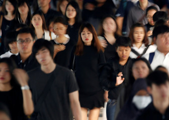 Passengers dressed in black and white or dark coloured clothes o mourn the passing of Thailand's King Bhumibol are seen in Bangkok