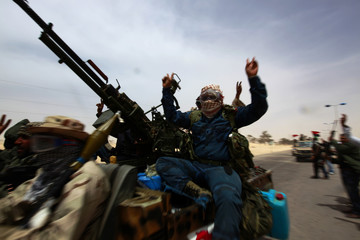 Rebel fighters head for the front line near Ajdabiyah