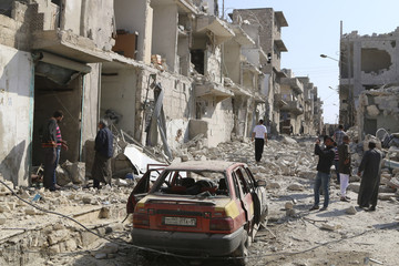 People inspect a damaged site hit by what activists said were barrel bombs dropped by forces loyal to Syria's President Bashar al-Assad in Aleppo's al-Sakhour district