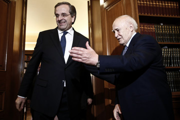 Greek President Papoulias welcomes Greece's Prime Minister Samaras before their meeting at the Presidential Mansion in Athens
