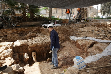 An Israeli Antiquities Authority archaeologist stands near a bathhouse, part of a find exposed in Jerusalem