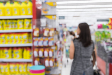 Blurred image of a woman with a shopping in the supermarket store.