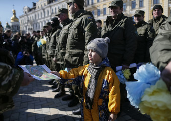 "A boy presents his painting to serviceman of the Ukrainian national guard battalion ""Donbass"" before they depart to the frontlines in eastern Ukraine, in central Kiev"