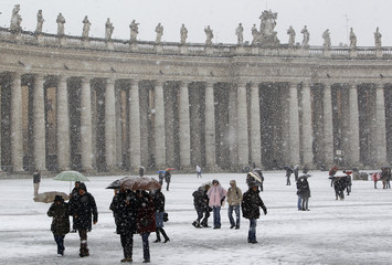 Tourists walk as it snows in Saint Peter's Square at the Vatican
