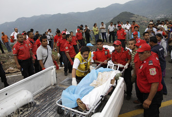 Members of a rescue team carry dead bodies next to the site of a passenger bus crash on a wet road in the southwestern state of Guerrero