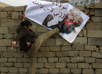 Afghan man kicks poster of Pakistani religious leader Maulana Fazlur Rehman during demonstration against his visit in Kabul
