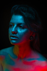 portrait of beautiful young woman with blue studio light