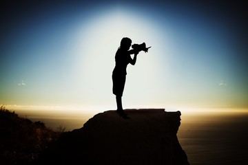 Composite image of silhouette businesswoman holding megaphone