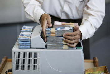A teller stacks Indonesian Rupiah on a currency counter inside a money changer in Jakarta, Indonesia,