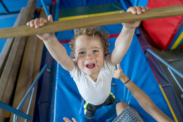 Male toddler doing pullups at a gym class.