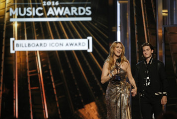 Billboard Icon Award recipient Celine Dion holds hands with her son Rene Charles as she accepts the award at the 2016 Billboard Awards in Las Vegas