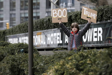 A boy stands with a sign protesting against U.S. Republican presidential candidate Donald Trump, outside the Trump International Hotel and Tower in New York