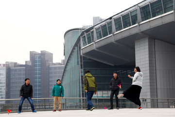 People kick a shuttlecock outside the headquarters of the New Oriental Education & Technology Group in Beijing