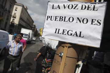 People walk past a sign at Madrid's Puerta del Sol