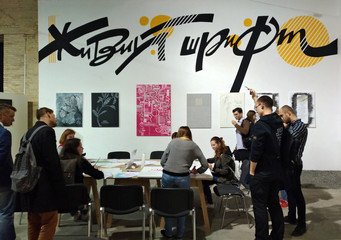 People learn calligraphy on the stand of calligraphy at the book exhibition in Arsenal, Kiev.
