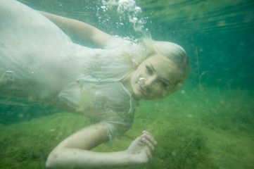 A floating woman. Underwater portrait. Girl in white dress swimming in the lake. Green marine plants and water