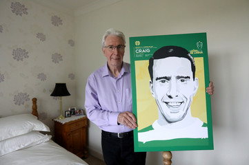 Lisbon Lion Jim Craig poses for a photograph with a print depicting him from the Lisbon Lions era at his home near Perth, central Scotland