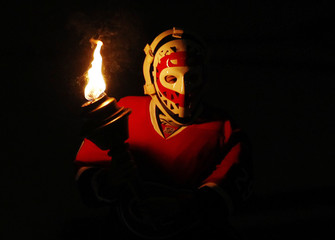A young hockey player wears the mask of Dryden as he holds a torch before the Canadiens play the Capitals in Game 6 of their NHL Eastern Conference in Montreal